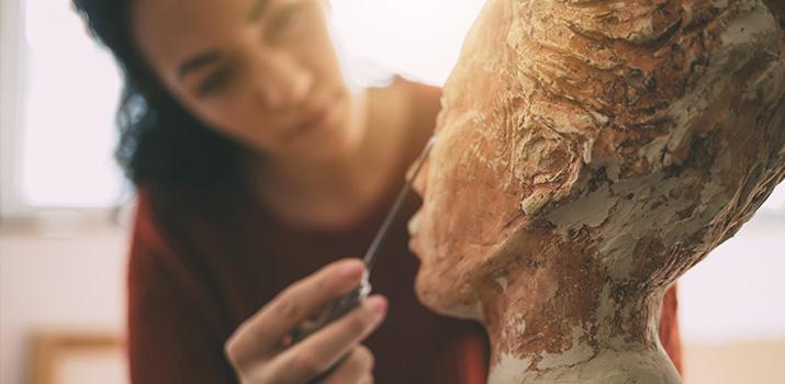 woman sculpting human bust